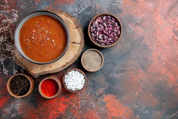 Draufsicht der klassischen tomatensuppe auf hölzernen tablettbohnen und verschiedenen gewürzen auf mischfarbtabelle