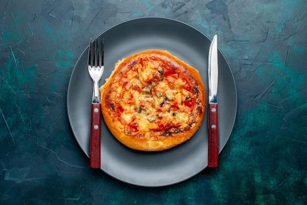 Draufsicht der kleinen käsepizza runde gebildet innerhalb platte auf dunkelblauer oberfläche