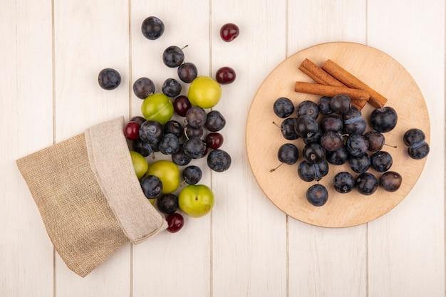 Draufsicht der kleinen sauren blau-schwarzen fruchtschleifen auf einem hölzernen küchenbrett mit zimtstangen mit grüner kirschpflaume und roten kirschen, die aus einem leinensack auf einem weißen hölzernen hintergrund fallen