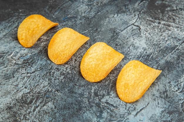 Draufsicht der knusprigen gebackenen chips, die in einer reihe auf grauem hintergrund aufgereiht sind