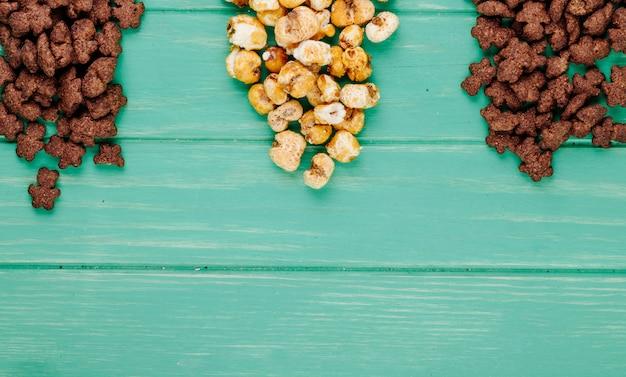 Draufsicht der knusprigen schokoladen-cornflakes und des karamellpopcorns auf grünem hintergrund mit kopienraum