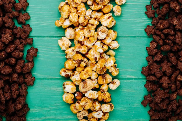 Draufsicht der knusprigen schokoladen-cornflakes und des karamellpopcorns auf grünem hölzernem hintergrund