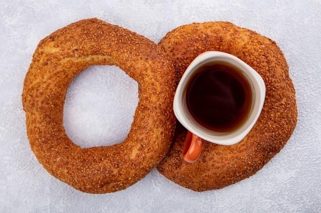 Draufsicht der knusprigen türkischen sesambagels mit einer tasse tee auf weißem hintergrund