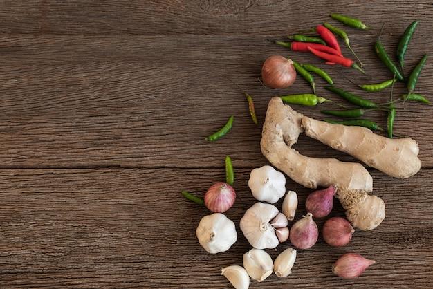 Draufsicht der kochenden bestandteile sind zwiebel, chili, ingwer und knoblauch auf einem hölzernen hintergrund. gewürze von thailand