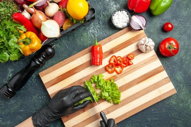 Draufsicht der köchin, die frischen grünen salat auf der grauen oberfläche schneidet