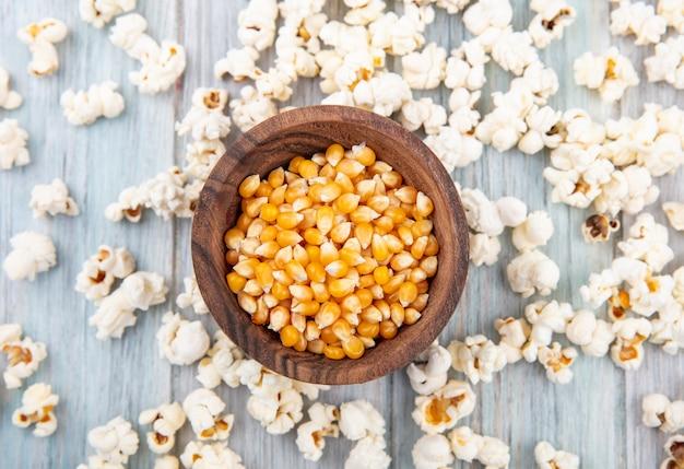Draufsicht der körner auf hölzerner schüssel mit popcorn lokalisiert auf grau