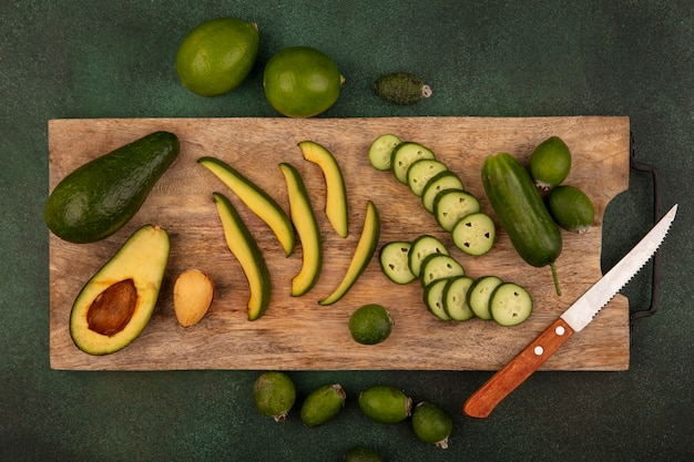 Draufsicht der köstlichen avocado mit scheiben auf einem hölzernen küchenbrett mit gurkenscheiben mit limetten und feijoas lokalisiert auf einer grünen oberfläche