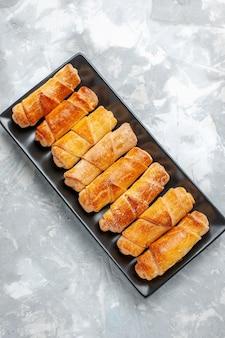 Draufsicht der köstlichen gebackenen armreifen auf hellgrauem schreibtisch, gebäckkuchen backen ofentee süß