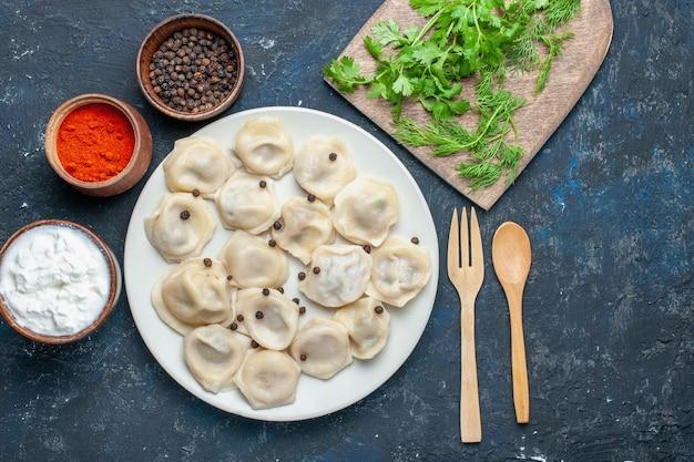 Draufsicht der köstlichen gebackenen knödel innerhalb des tellers zusammen mit pfeffer und grün auf dunklem schreibtisch, teigmahlzeitnahrungsmittelessen-fleischkalorie