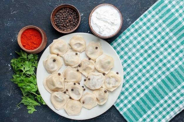 Draufsicht der köstlichen gebackenen knödel innerhalb des tellers zusammen mit pfefferjoghurt und -grün auf grauem schreibtisch, teigmahlzeit-abendessenfleischkalorie