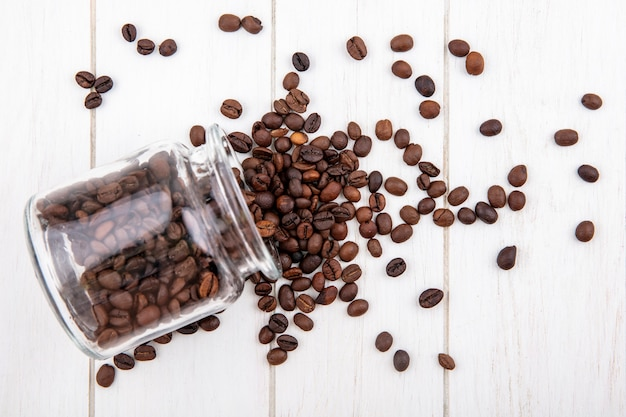 Draufsicht der köstlichen kaffeebohnen, die aus einem glas auf einem weißen hölzernen hintergrund fallen