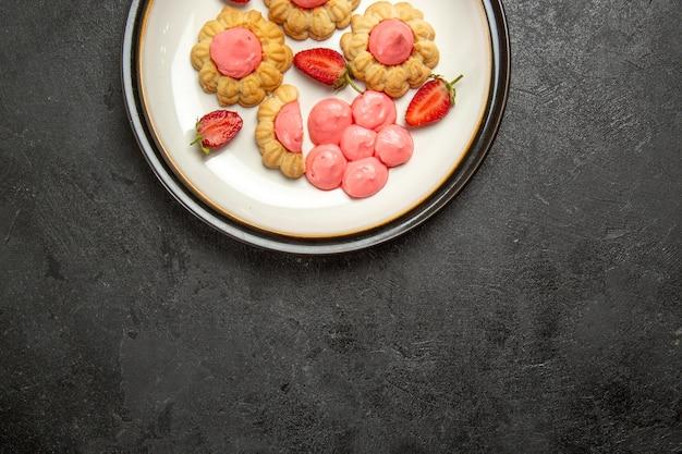 Draufsicht der köstlichen kleinen kekse mit rosa creme-innenplatte auf grauer oberfläche
