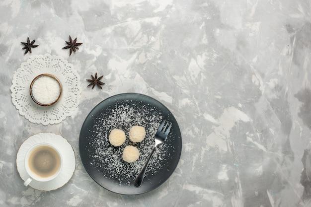 Draufsicht der köstlichen kokosnussbonbons mit kaffee auf weißem schreibtisch