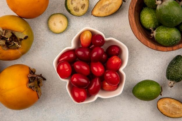 Draufsicht der köstlichen kornelkirschen auf einer schüssel mit feijoas und kakis lokalisiert auf einem grauen hintergrund