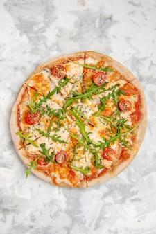 Draufsicht der köstlichen pizza mit tomatengrün auf befleckter weißer oberfläche