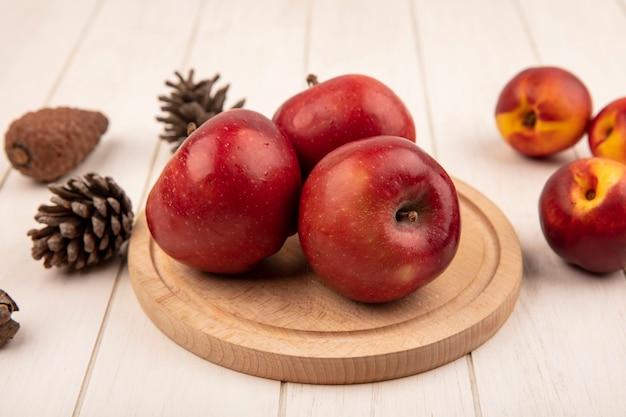Draufsicht der köstlichen roten äpfel auf einem hölzernen küchenbrett mit pfirsichen und tannenzapfen lokalisiert auf einer weißen holzoberfläche