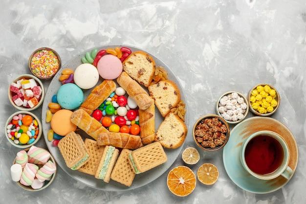 Draufsicht der köstlichen süßekompositionskuchenscheiben macarons-bonbons mit tasse tee auf weißer oberfläche