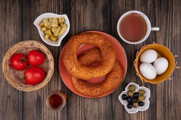 Draufsicht der köstlichen türkischen sesambagels auf einem teller mit oliven auf einer schüssel mit tomaten auf einem eimer und mit einer tasse tee auf einem hölzernen hintergrund