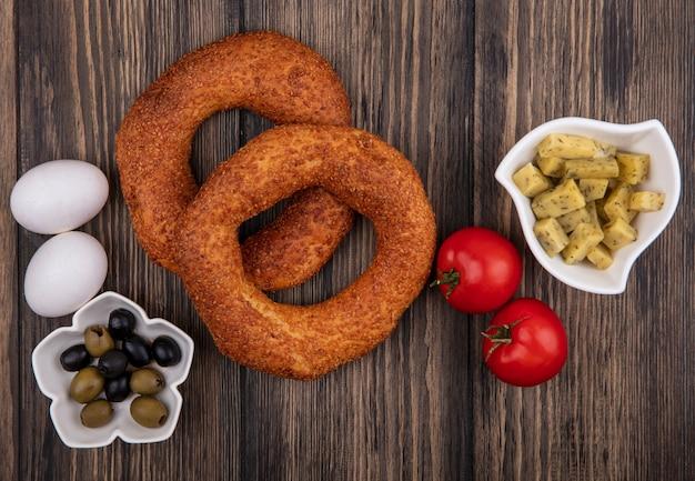 Draufsicht der köstlichen türkischen sesambagels mit oliven auf einer schüssel mit tomaten und eiern lokalisiert auf einem hölzernen hintergrund