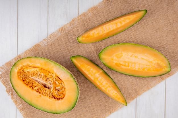 Draufsicht der köstlichen und frischen melone mit scheiben auf sackleinen auf weißem holz