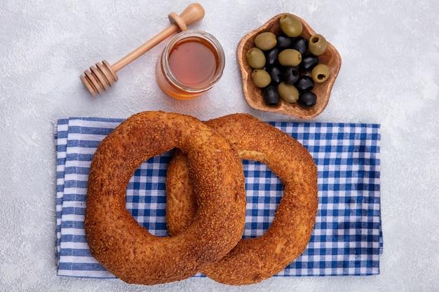 Draufsicht der köstlichen und weichen traditionellen türkischen bagels lokalisiert auf einem karierten tuch mit honig auf einem glas und oliven auf einer holzschale auf einem weißen hintergrund