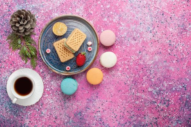 Draufsicht der köstlichen waffeln mit französischen macarons und einer tasse tee auf rosa oberfläche