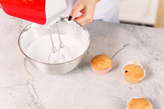 Draufsicht der konditorin mischt eine weiße creme in einer tiefen metallplatte mit rotem küchenmixer für frisch gebackene cupcakes.