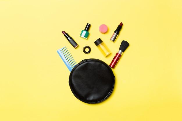 Draufsicht der kosmetiktasche mit verschütteten make-up-produkten auf gelbem hintergrund. schönheitskonzept mit leerem raum für ihr design