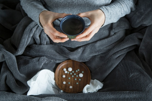 Draufsicht der kranken frau auf sofa, grüne schale in den händen halten