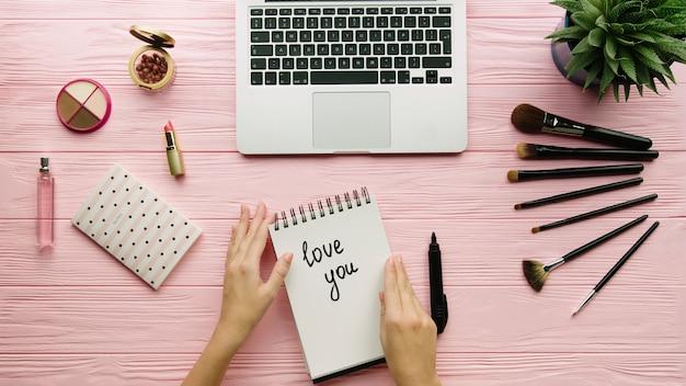 Draufsicht der kreativ dekorierten komposition mit kosmetik, make-up-werkzeugen, zubehör und frauenhänden, die auf notizbuch auf farboberfläche schreiben. beauty-, mode- und einkaufskonzept.