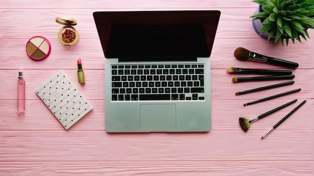 Draufsicht der kreativ dekorierten komposition mit kosmetik, make-up-werkzeugen, zubehör und laptop auf farboberfläche. beauty-, mode-, party- und einkaufskonzept.