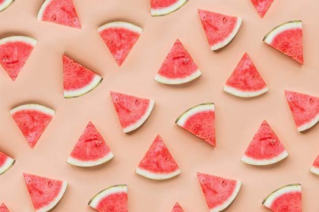 Draufsicht der kreativen ebenenlage von neuen wassermelonenscheiben auf orange tabellenhintergrund