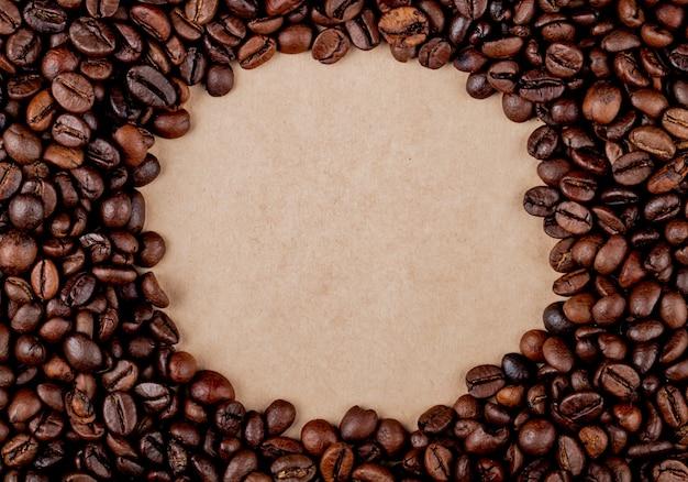 Draufsicht der kreiskaffeebohnen auf braunem papierbeschaffenheitshintergrund