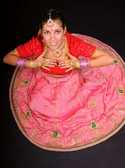 Draufsicht der lächelnden kaukasischen weißen frau, die im traditionellen indischen kostüm sitzt und hände nahe brust hält. dunkler hintergrund