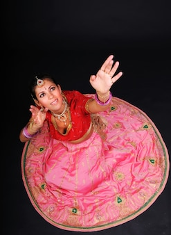 Draufsicht der lächelnden kaukasischen weißen frau, die im traditionellen indischen kostüm sitzt und hände oben hält. dunkler hintergrund