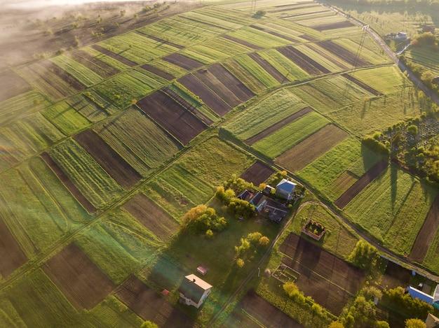 Draufsicht der ländlichen landschaft am sonnigen frühlingstag. bauernhaus, häuser und scheunen auf grünen und schwarzen feldern. drohnenfotografie.