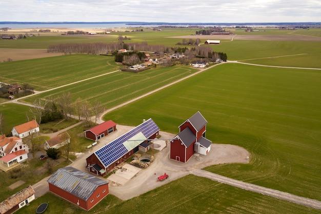 Draufsicht der ländlichen landschaft am sonnigen frühlingstag. bauernhof mit solar-photovoltaik-system auf holzgebäude, scheune oder hausdach. kopierbereich auf der grünen wiese. erzeugung erneuerbarer energie.