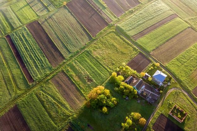 Draufsicht der ländlichen landschaft am sonnigen frühlingstag. bauernhofhäuschen, -haus und -scheune auf grünem und schwarzem feld kopieren raumhintergrund. drohnenfotografie.