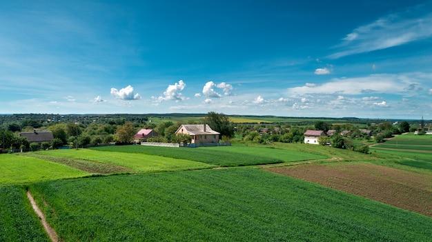 Draufsicht der ländlichen landschaft am sonnigen frühlingstag. haus und grünes feld. drohnenfotografie