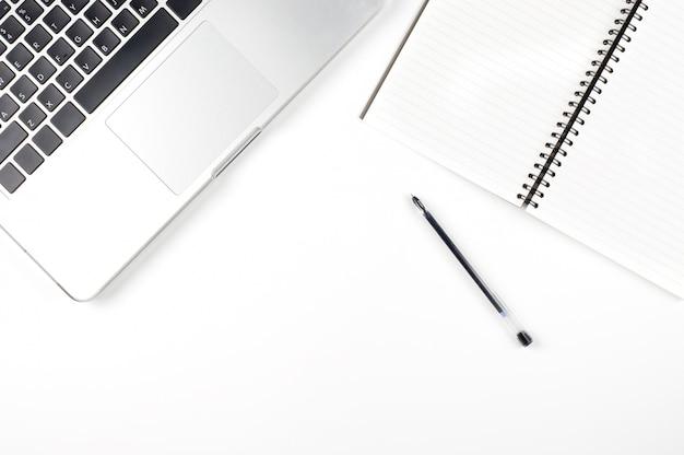 Draufsicht der laptop-computers, des balnk notizbuches und des stiftes auf weiß