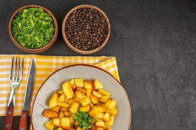 Draufsicht der leckeren bratkartoffeln innerhalb des tellers mit grüns auf der dunkelgrauen oberfläche
