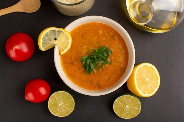 Draufsicht der leckeren gemüsesuppe innerhalb platte mit zitronenscheibenöl und roten tomaten auf dunkler oberfläche