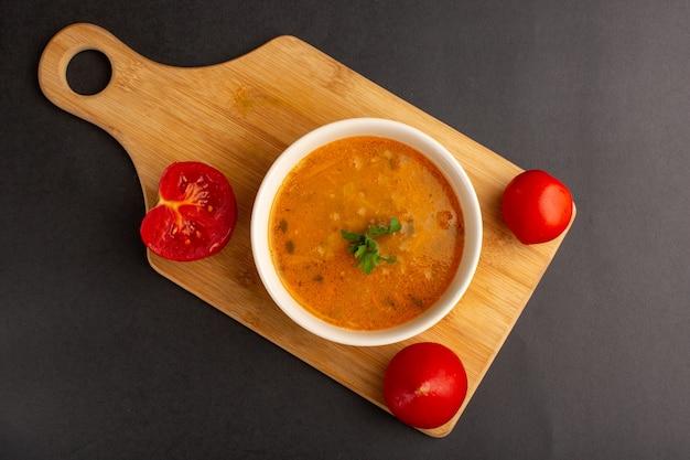 Draufsicht der leckeren gemüsesuppe innerhalb platte zusammen mit tomaten auf dunkler oberfläche