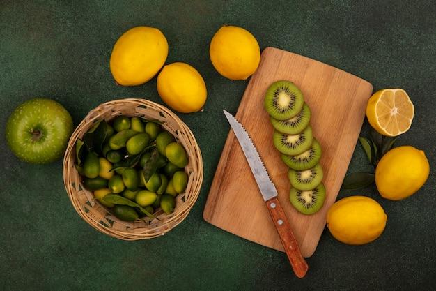 Draufsicht der leckeren kiwischeiben auf einem hölzernen küchenbrett mit messer mit kinkans auf einem eimer mit zitronen und apfel lokalisiert auf einer grünen oberfläche