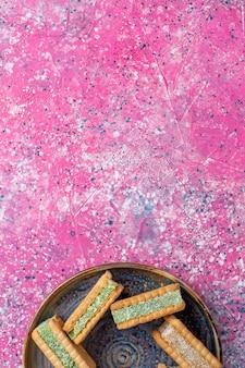 Draufsicht der leckeren waffelkekse innerhalb der platte auf der rosa oberfläche