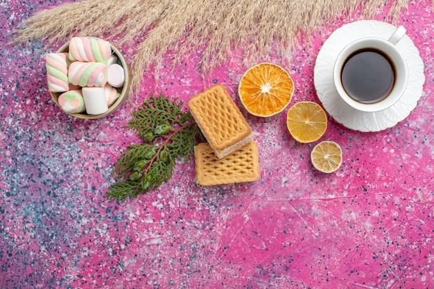 Draufsicht der leckeren waffelkekse mit tasse tee und marshmallows auf rosa oberfläche