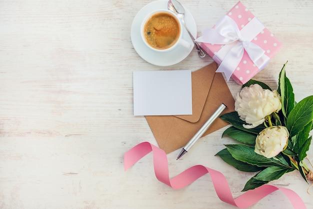 Draufsicht der leeren anmerkung, des kraftpapier-umschlags, der kaffeetasse und der pfingstrose blüht über weißem hölzernem rustikalem, copyspace.