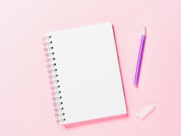 Draufsicht der leeren notiz mit stift auf rosa hintergrund