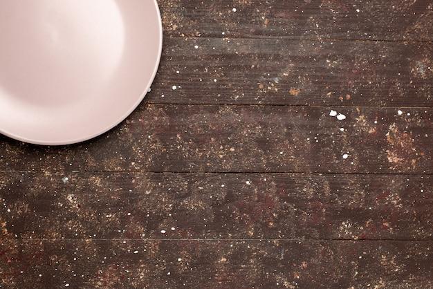 Draufsicht der leeren platte, die auf braunem rustikalem plattenlebensmittelküchenholz rosa gefärbt wird