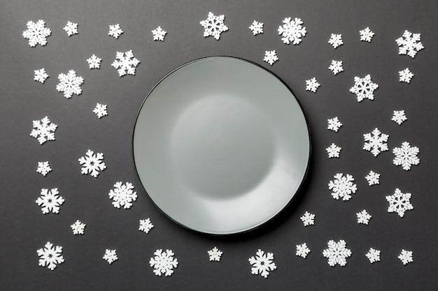 Draufsicht der leeren platte umgeben mit schneeflocken auf bunter oberfläche.